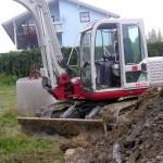 Bauarbeiter im Bagger beim Kanalausheben