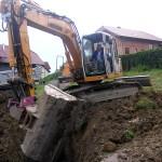Mensch im Bagger bei Kanalarbeiten